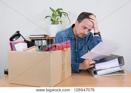 Desperate Man Reading A Dismiss Notification, Preparing His Box