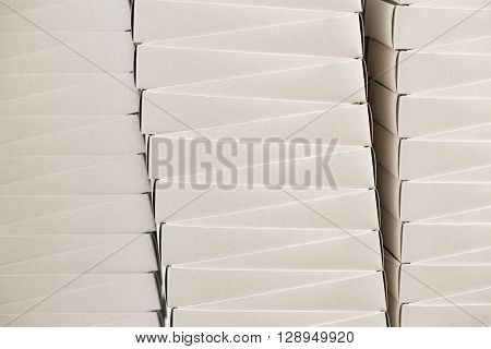 Plain white boxes. Stack of white carton boxes. Inexpensive food containers in warehouse. Free delivery of cheap merchandise.