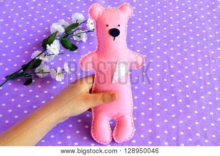 Children hand holds a pink felt Teddy bear