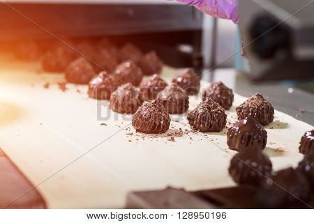 Brown sweets on beige cloth. Dark candies with shavings. Dream of a gourmet. Special recipe of savoury dessert.