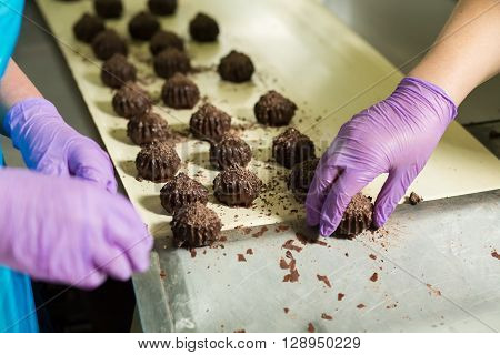 Hand in glove takes candy. Dark brown sweets on cloth. Dessert popular among cafe clients. Pieces of artwork.