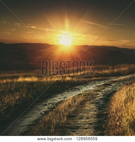 Travel and adventure backgrounds with country road between golden hills