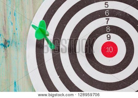 dart arrow missed in the target center of dartboard