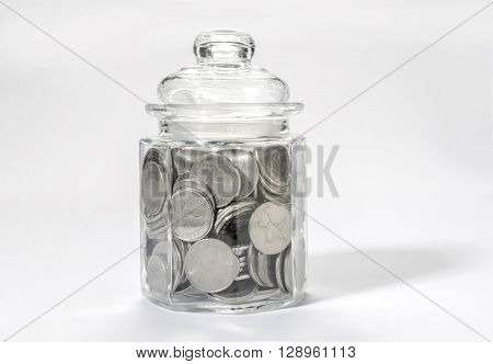 Saving money - a concept. UAE dirham coins in a glass bottle.