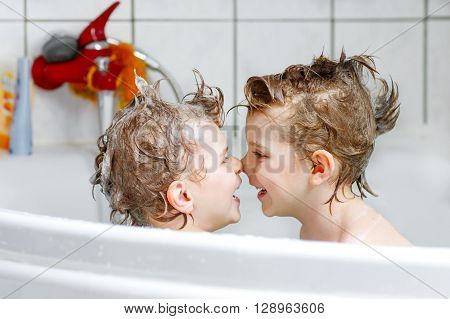 Happy siblings: Two little twins children playing together with water by taking bath in bathtub at home. Kid boys having fun together. poster