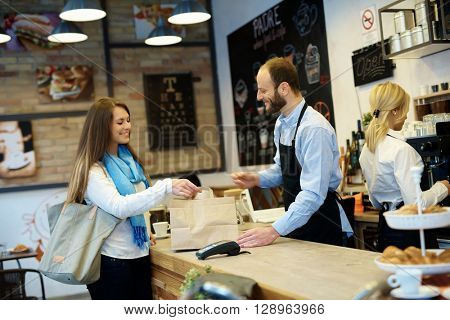 Waiter serving guest in cafeteria. Placing takeaway order on counter.
