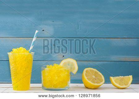 Fresh lemon slushie on blue wood background
