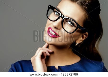Optics style. Portrait of a beautiful young woman wearing elegant glasses. Beauty, fashion. Cosmetics, make-up.