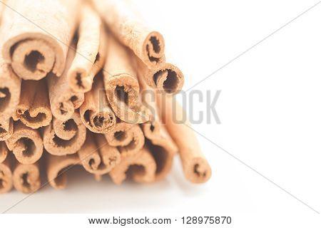 Artistic view of Raw Organic Cinnamon sticks (Cinnamomum verum) isolated on white background.