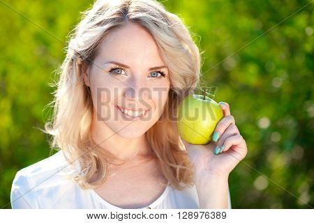 Smiling girl 20-24 year old holding green apple outdoors closeup. Looking at camera. Posing over green nature background. Healthy eating.