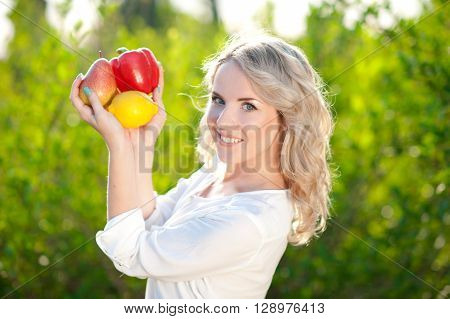 Smiling blonde girl 20-24 year old holding organic food outdoors. Posing over nature background. Looking at camera. Healthy lifestyle.