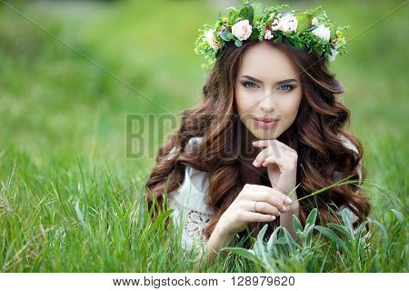 Spring portrait of a beautiful woman in a wreath of flowers,long curly red hair,gray eyes,light makeup and a beautiful smile,dressed in a white summer dress,lying on the soft green grass outdoors in spring