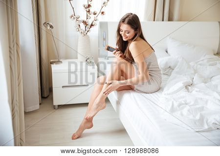 Charming woman applying cream on legs on the bed at home