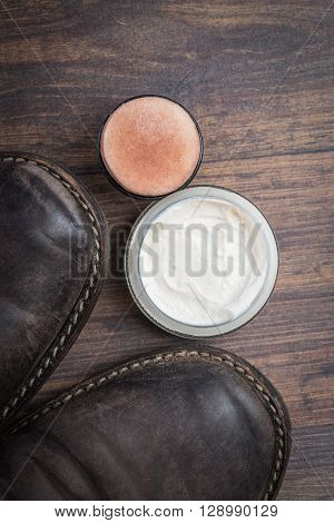Old Worn Out Brown Leather Shoes With Cream Over The Dark Background