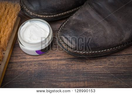 Old Worn Out Brown Leather Shoes With Cream And Brush Over The Dark Background