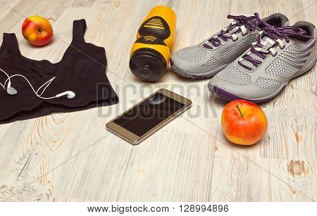 Sport shoes and water bottle with sports equipment on wooden floor.