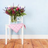Chair with vase mixed bouquet flowers on blue background poster
