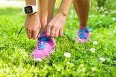 Active lifestyle smartwatch runner woman tying running shoes. Healthy summer living. Sports girl getting ready for weight loss run exercise lacing footwear laces wearing activity tracker wristwatch. poster
