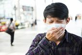 Asian young man feeling unwell at outdoor poster