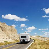 Recreational vehicle on scenic road in Badlands National Park, North Dakota.