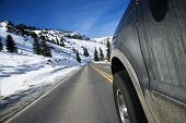 Perspective shot of SUV driving down road in snowy Colorado during winter.