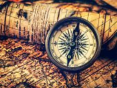 Travel geography navigation concept background - vintage retro effect filtered hipster style image of old vintage retro compass on ancient world map poster