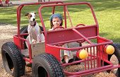 girl sits in a play car with her dog poster