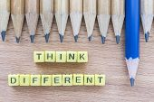 Words Think Different motivational slogan on wooden table with group of pencils. Top view. Think Different business unique and success concept poster