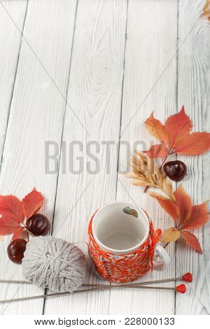 Autumn Still Life Cup Of Coffee On Wooden Table. Nitted Sweater With Autumn Leaves, Spokes, Crochet