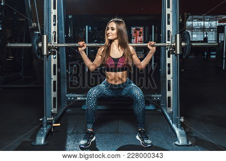 Beautiful Fitness Young Girls Doing Squats With The Barbell In Smith Machine At The Gym. Perfect Fit
