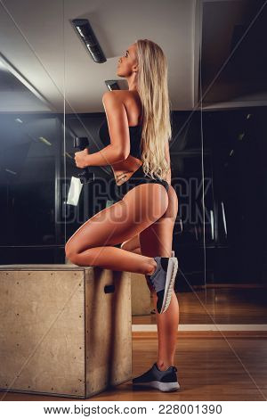 Sexy Blond Woman In Denim Shorts Standing On Knee And Holding One Dumbbell.
