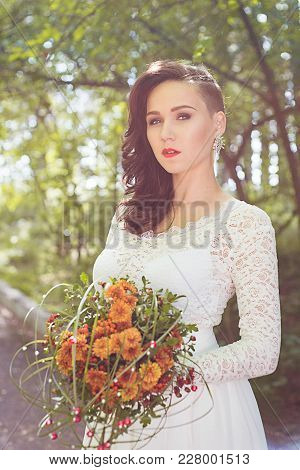 Close Up Portrait Of Young Beautiful Woman Bride In White Dress Looking Forward, Holds A Wedding Bou