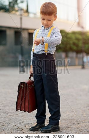 Concept Future Businessman. Full Length Boy Portrait In Dark Blue Pants, Baby Blue Shirt And Yellow