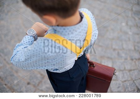 Up Back View Of Businessman In Blue Shirt Looking To His Silver Watch On The Hand, With Briefcase An