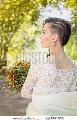 Profile Portrait Of Young Beautiful Woman Bride In White Dress, Holds A Wedding Bouquet In His Hand
