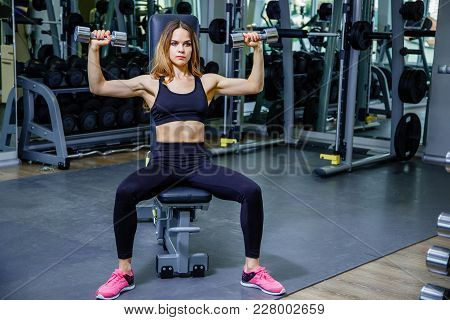 Attractive Girl Doing Dumbbell Exercises In Gym.