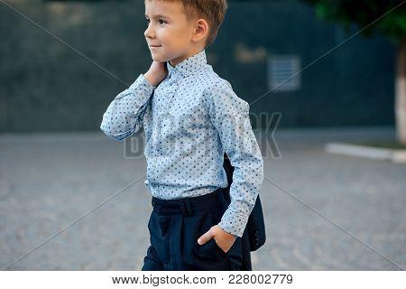 Portrait Elegant Little Man In Fashionable Navy Blue Shirt Holding Dark Blue Jacket On His Back Smil