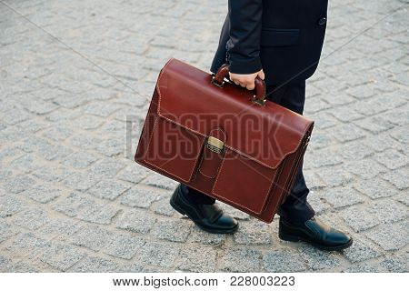 Close Up Shot Of Future Businessman Holding Leather Briefcase While Walking On Pavage Street Outdoor
