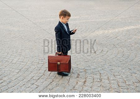 Concept Future Businessman. Side Angle Of  Smiling Businessman In Formal Wear Standing On Pedestrian
