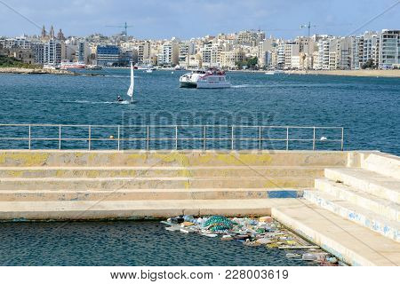 Swimming Pool With Waste Floating In The Water At Valletta, Malta
