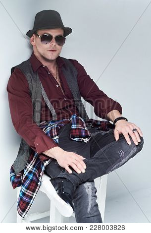 Portrait Of Casual Male Dressed In A Shirt, Waistcoat And Sunglasses Sits On A Chair.