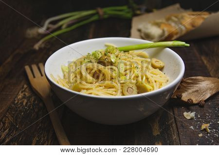 Close Up Shot Of A White Bowl Filled With Spaghetti Pasta And Olives
