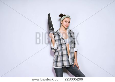 Attractive Young Girl Holding A Sharp Saw In Her Hand, Wants To Make Repairs In The Apartment