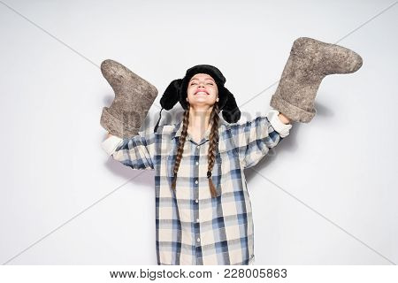 Happy Young Russian Girl In A Warm Fur Hat Holds A Pair Of Felt Boots