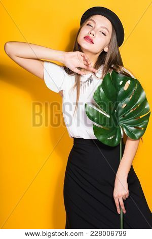 Attractive Young Girl Model In Fashionable Clothes Posing With Green Leaf