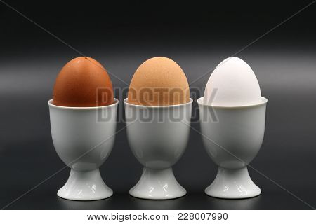 Brown To White Three Breakfast Eggs In Eggcup Isolated On Black Background