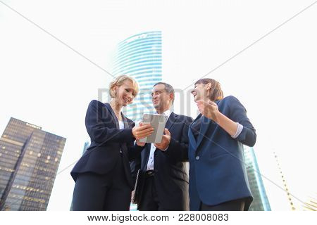 Satisfied Business Team Members Speaking Outdoors In  . Concept Of Biz Partners Enjoying Successful