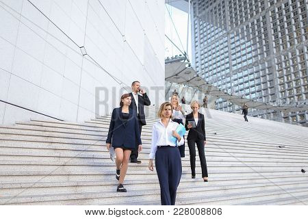 Financial Team Members Going Down Stairs With Tablet, Document Case And Talking By Smartphone In  .