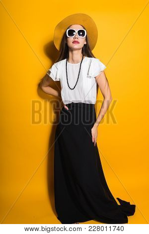 Attractive Model Girl In Fashion Hat And Sunglasses Posing On Yellow Background, Stylish Clothes