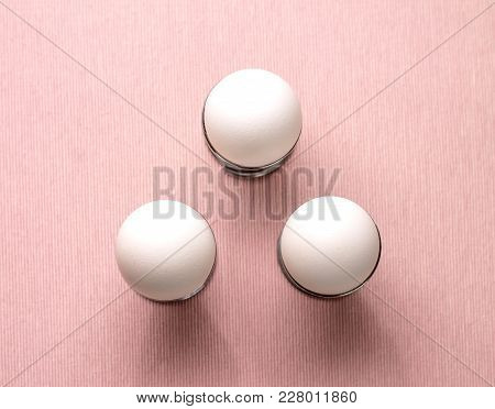 Top View Of Three White Eggs In Egg Cup On Pink Background Isolated. Design, Visual Art, Minimalism